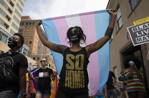 Person holds up pink, blue and white stripe flag.
