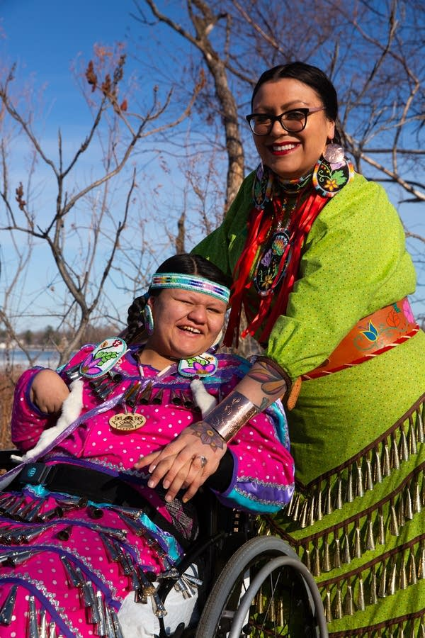woman stands with daughter in wheelchair wearing traditional regalia