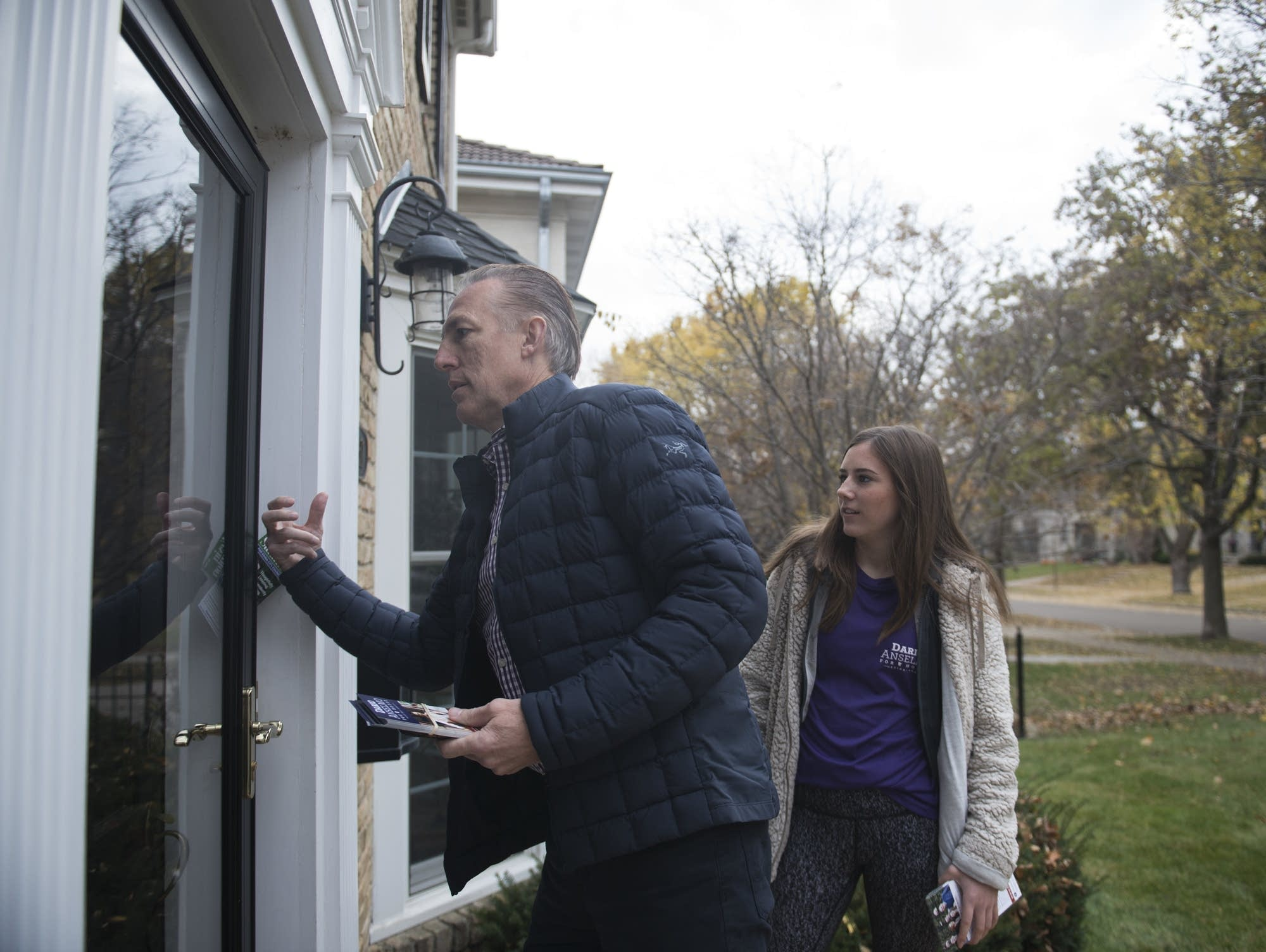 Dario Anselmo knocks on a door with his daughter Ali in Edina.