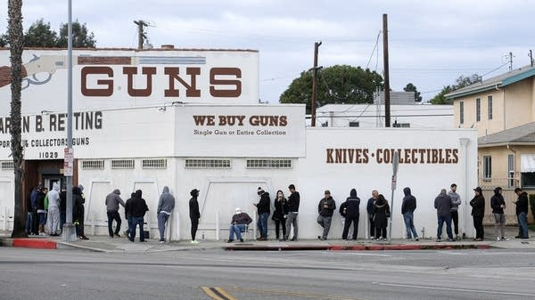 People wait in a line to enter a gun store