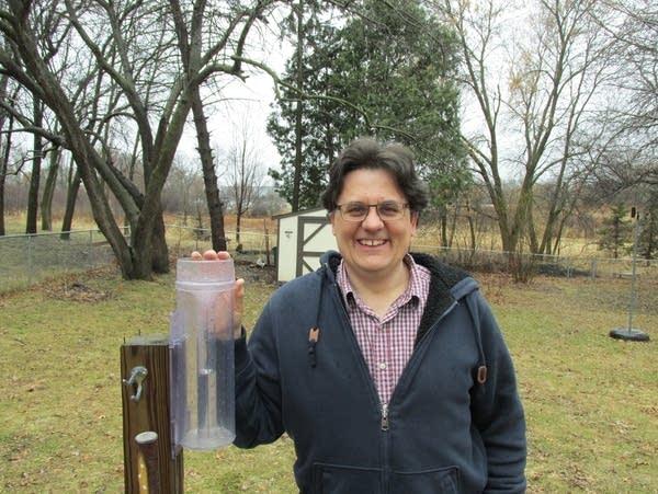 A man stands next to a rain gauge