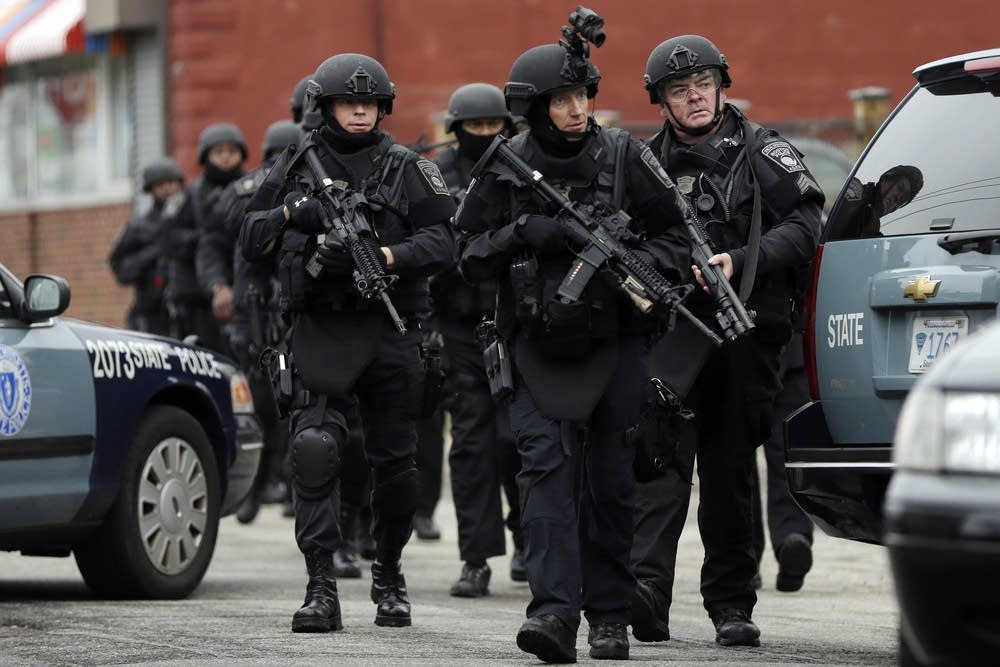Police in tactical gear conduct a search