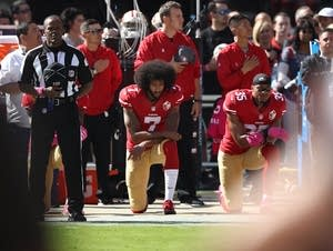 Colin Kaepernick 017 of the San Francisco 49ers kneel.