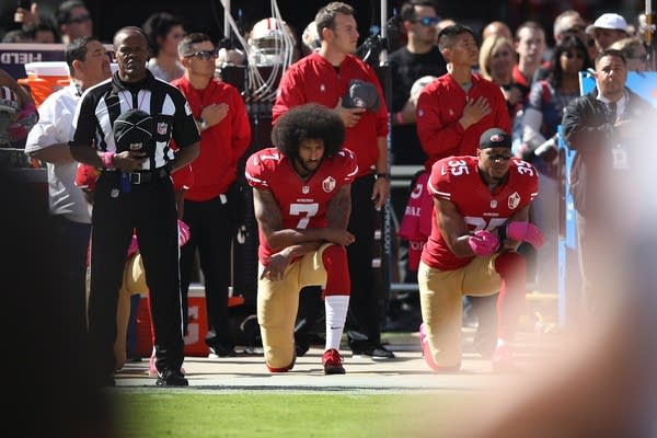 Colin Kaepernick 017 of the San Francisco 49ers kneel.