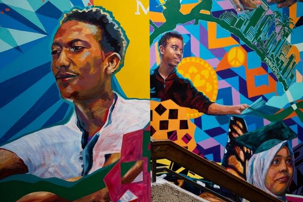 A mural depicts students above a staircase.