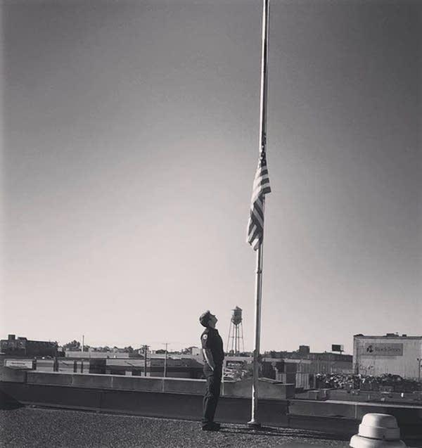 A man stands beside a flag at half staff.