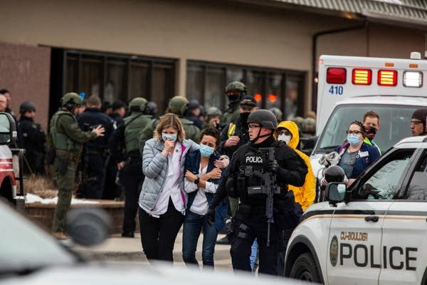 Health care workers walk out of a grocery store after a shooting.