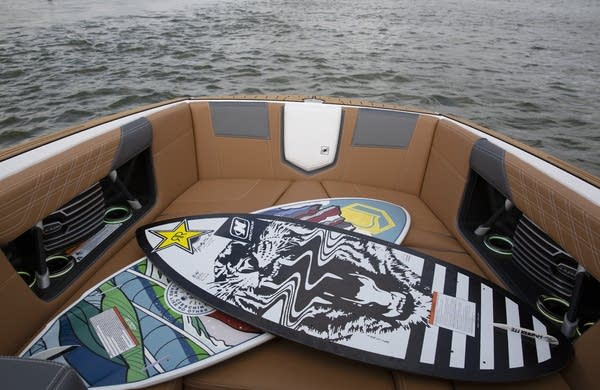 Two wakesurf boards are placed on tan seats in a boat's bow.