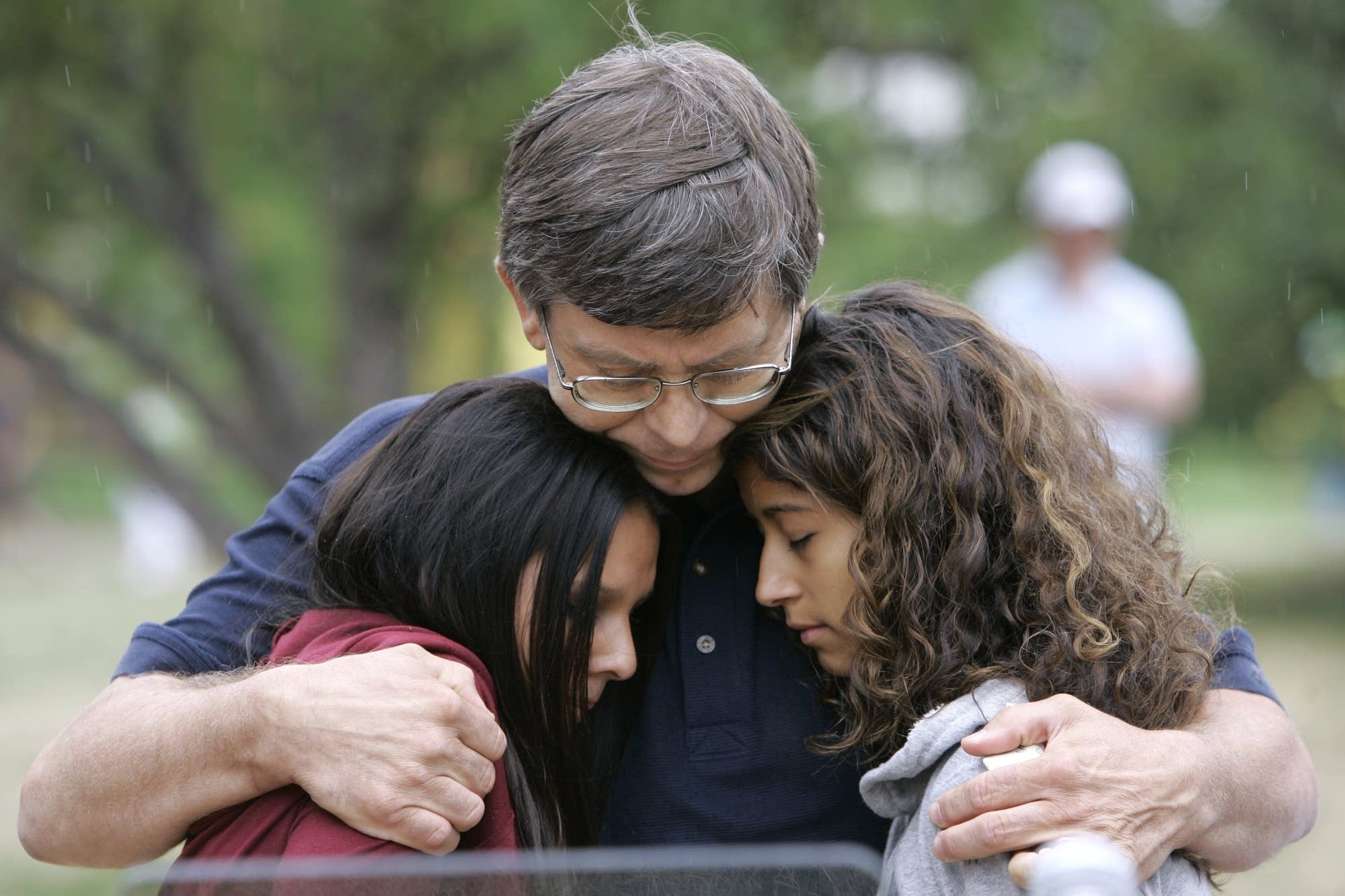 Ron Engebretsen hugs his daughters. His wife died in the bridge collapse.