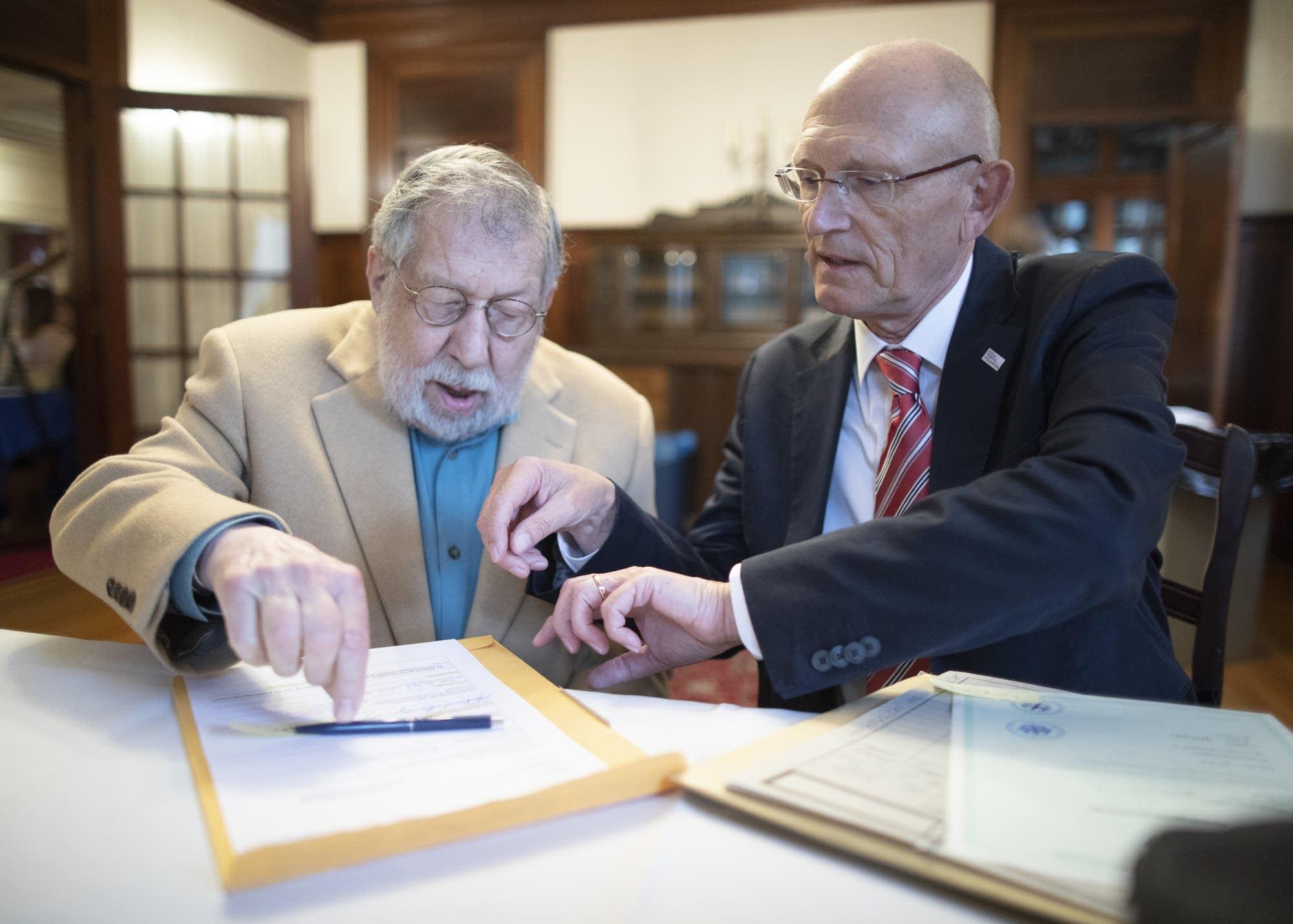 Fred Amram (left) signs citizenship documents.