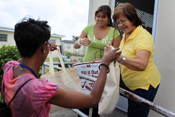 U.S. Census worker Monique Stence, left, gives out census bags.