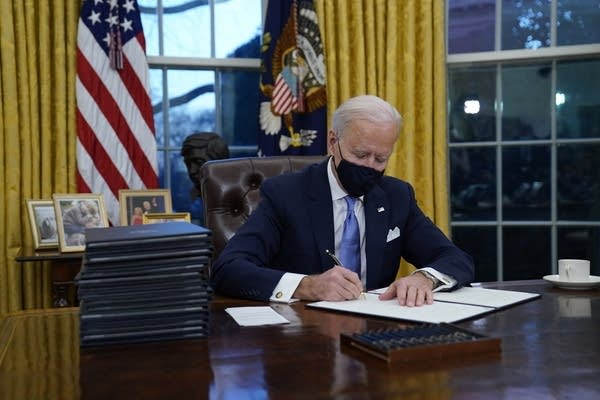 President Joe Biden signs his first executive orders in the Oval Office.
