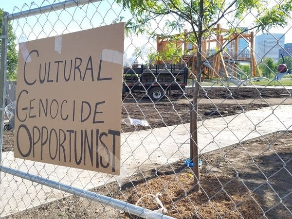 """Signs of protest against the work """"Scaffold"""" at the Walker Art Center"""