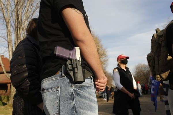A gun strapped on someone's hip.