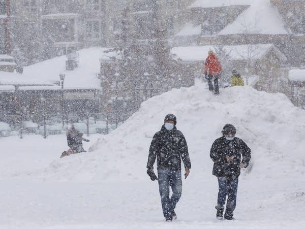 People walk through the snow