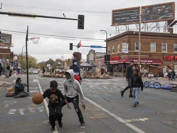 Kids play basketball in the street.