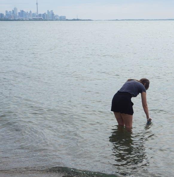 Une femme se tient jusqu'aux genoux dans le lac et se penche avec un conteneur.