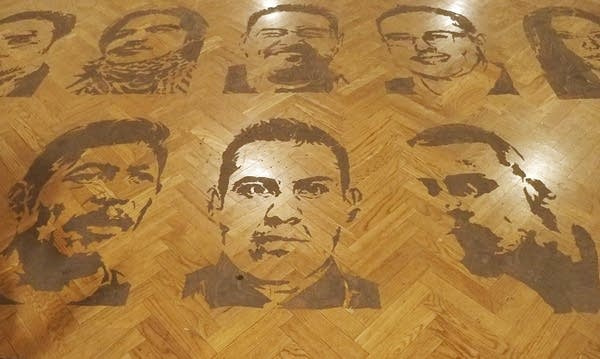 Faces are printed in mud on a wooden floor.