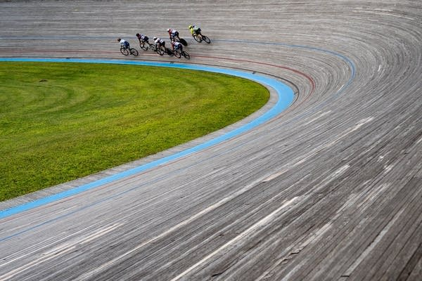 The curve of the track leads left to a group of cyclists.