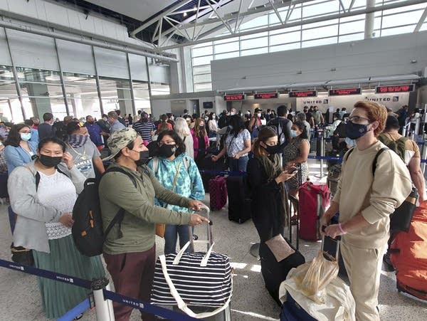 Airline passengers wearing masks wait to check in