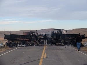 Burned vehicles block a bridge