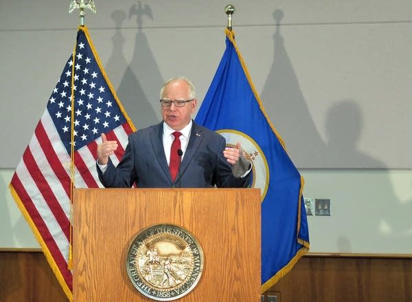 A man stands in front of flags as he speaks at a podium.