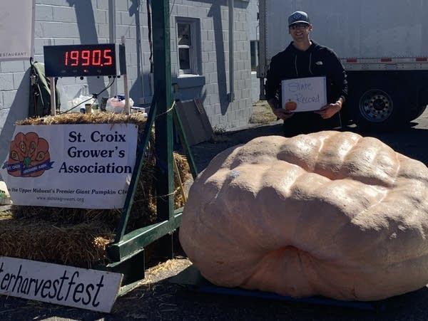 A man stands by a large pumpkin.
