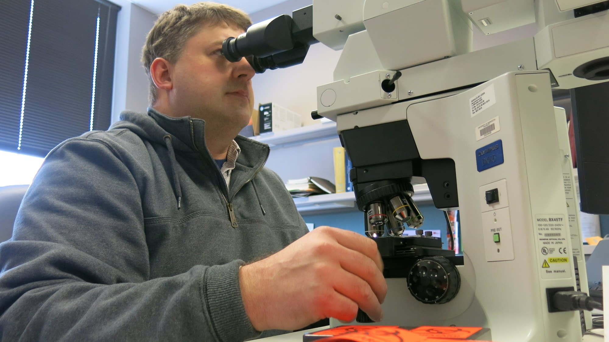 Schefer squints through a microscope, looking for any sign of CWD
