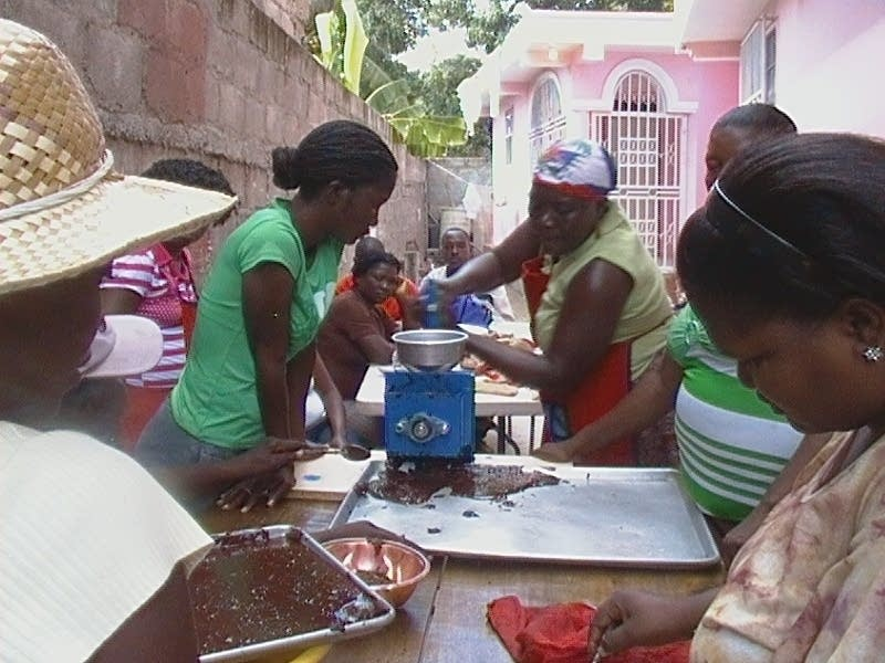Women grinding cocoa beans in Haiti