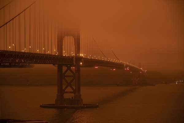 Cars drive along the San Francisco Bay Bridge under a smoky sky.