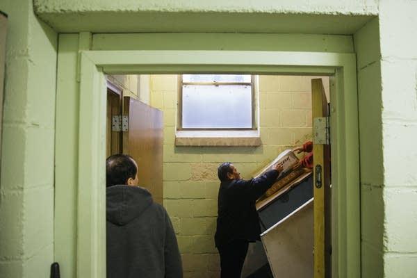 Volunteers slide food donations into the basement.