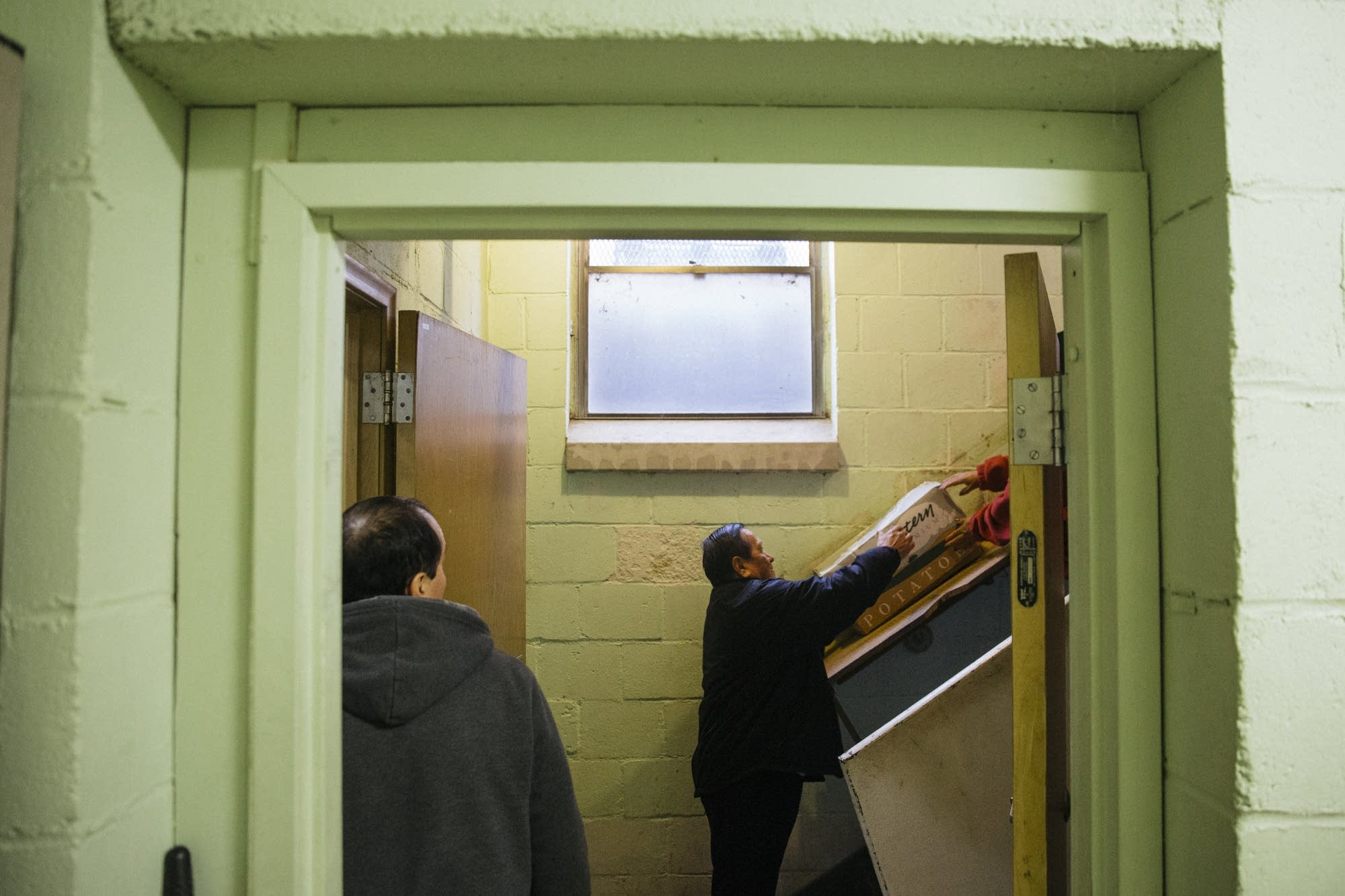 Volunteers slide food donations into the basement.