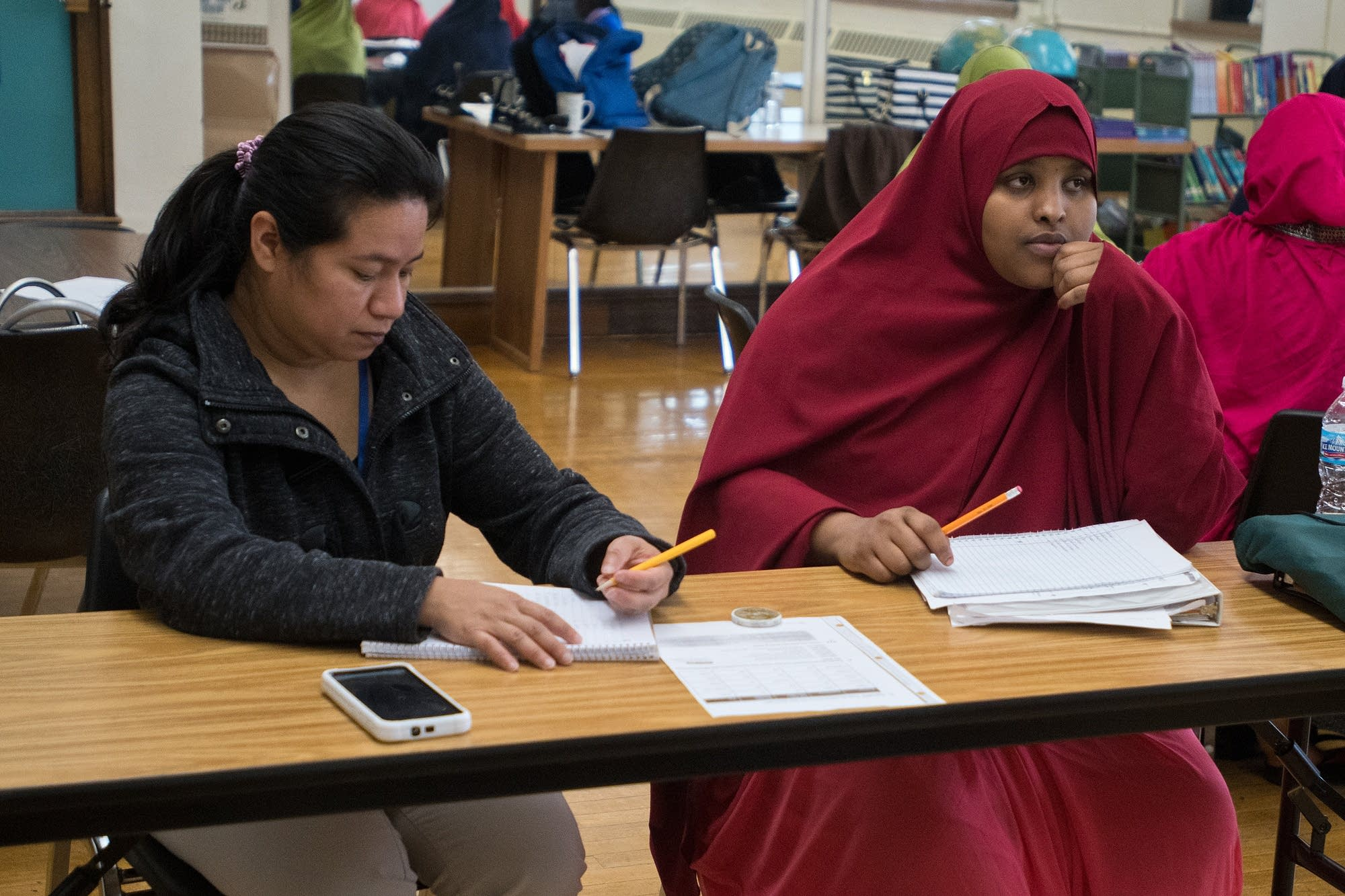 Muno Warsame and Julia Lopez take notes during an English class.