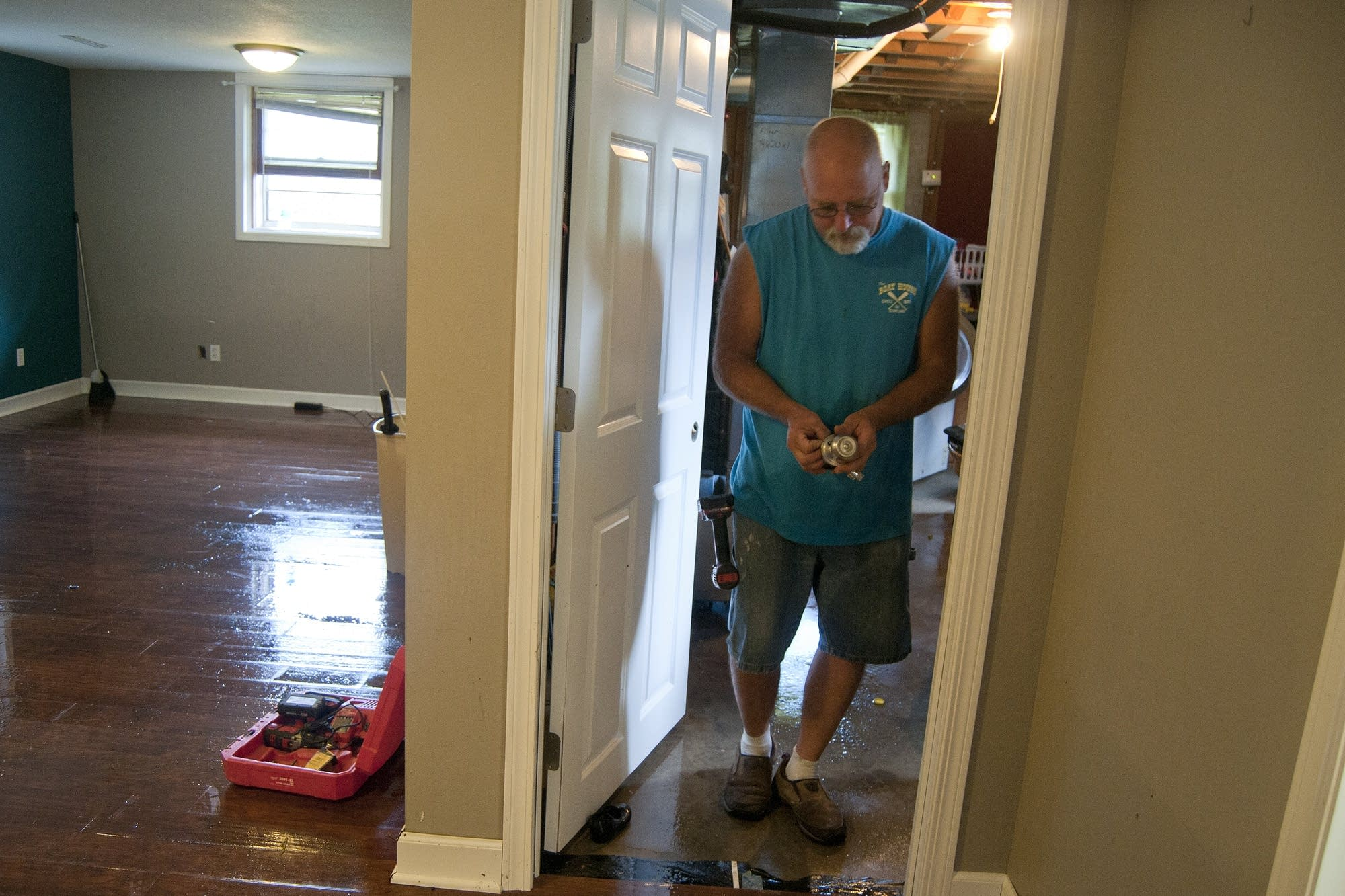 Mike Kuster salvages knobs from a flooded basement