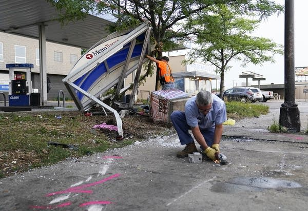 People clean up debris at the site of a crash.