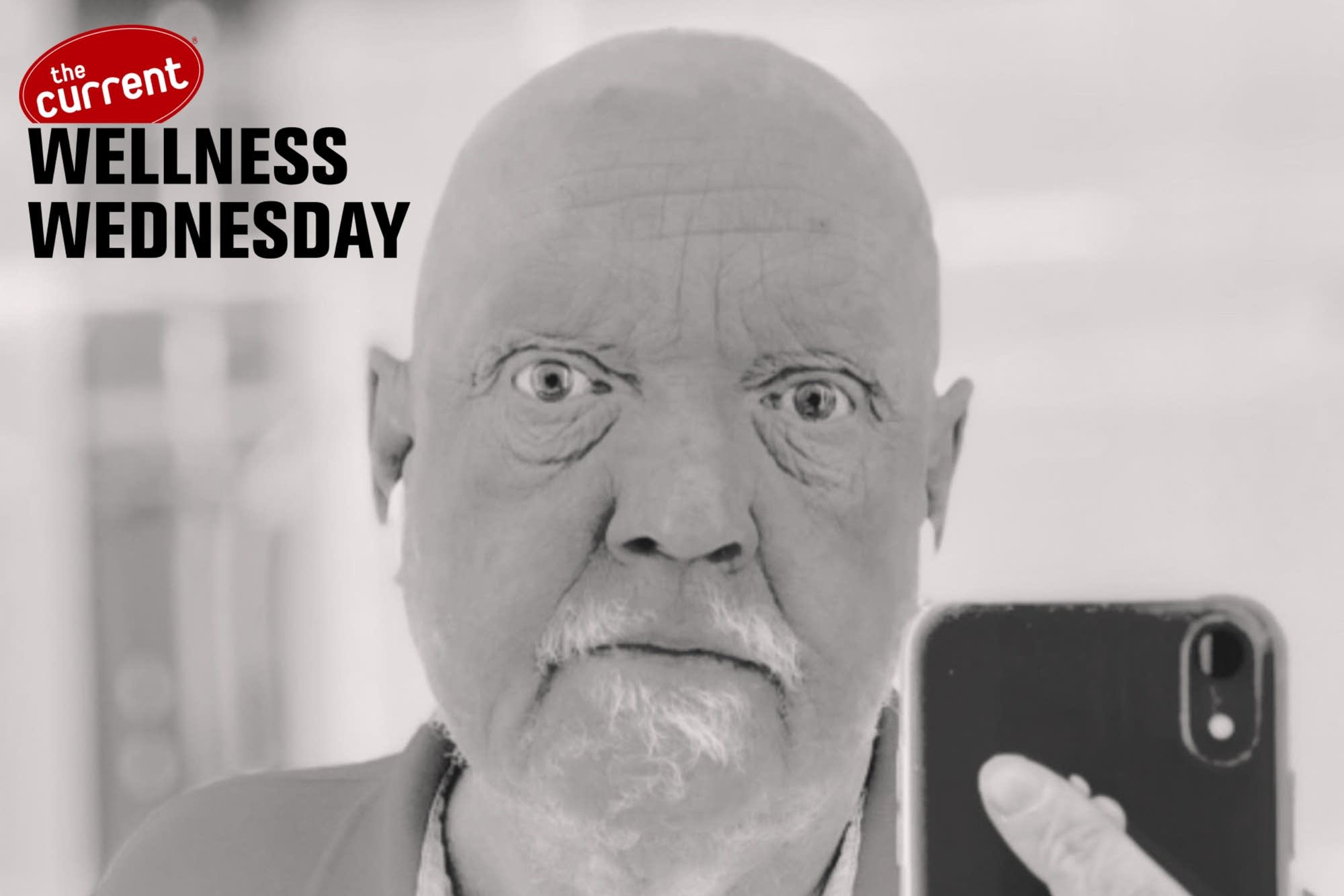 Man holding phone with Wellness Wednesday logo overlaid.