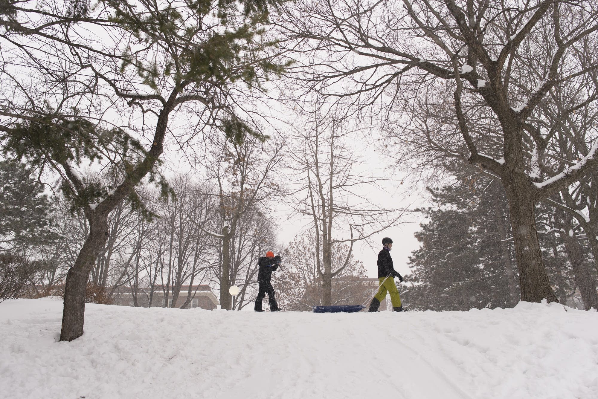 Mark Lutterman and his son John walk across the top of a sledding hill.