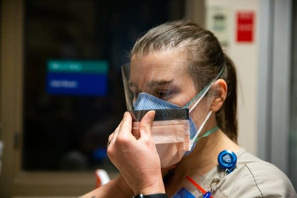 A woman puts on a face shield over a face mask.