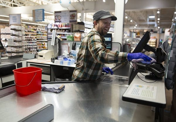 A person sanitizes a credit card machine at a grocery store