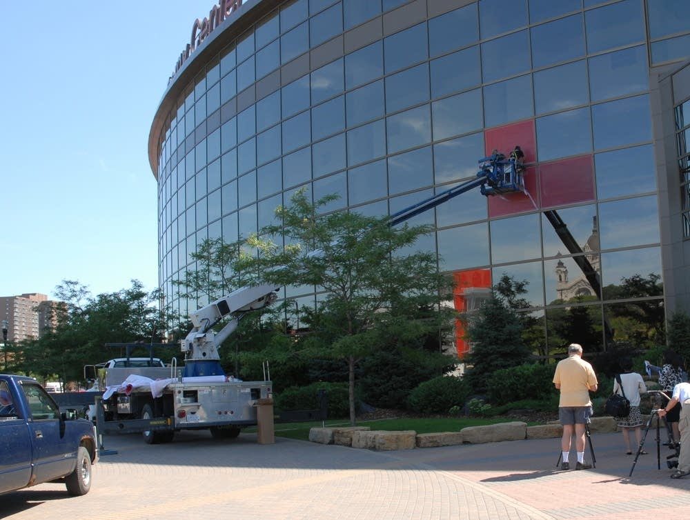 Workers wrap the facade of the Xcel Center