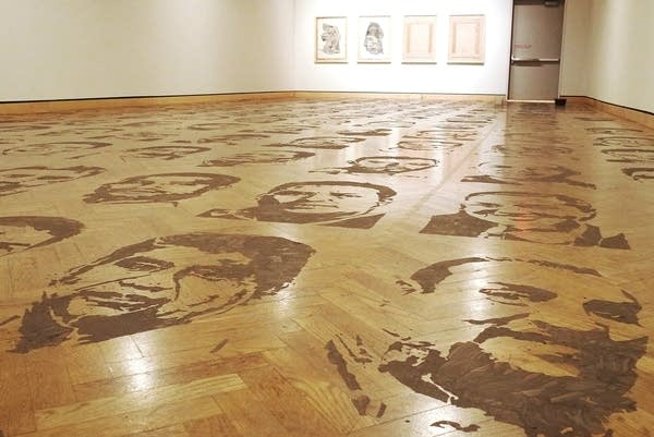 Faces printed in mud cover a wooden floor in an art gallery.