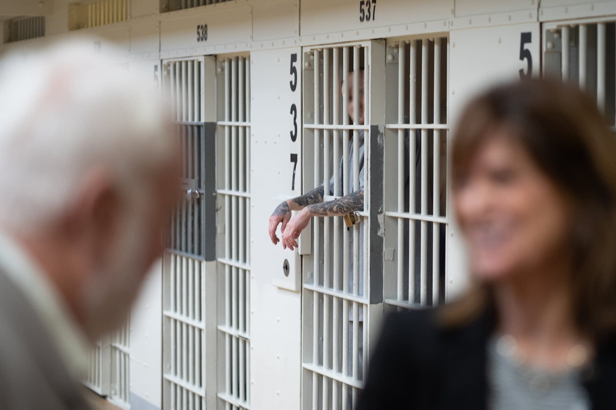 An inmate watches government officials tour Stillwater prison.