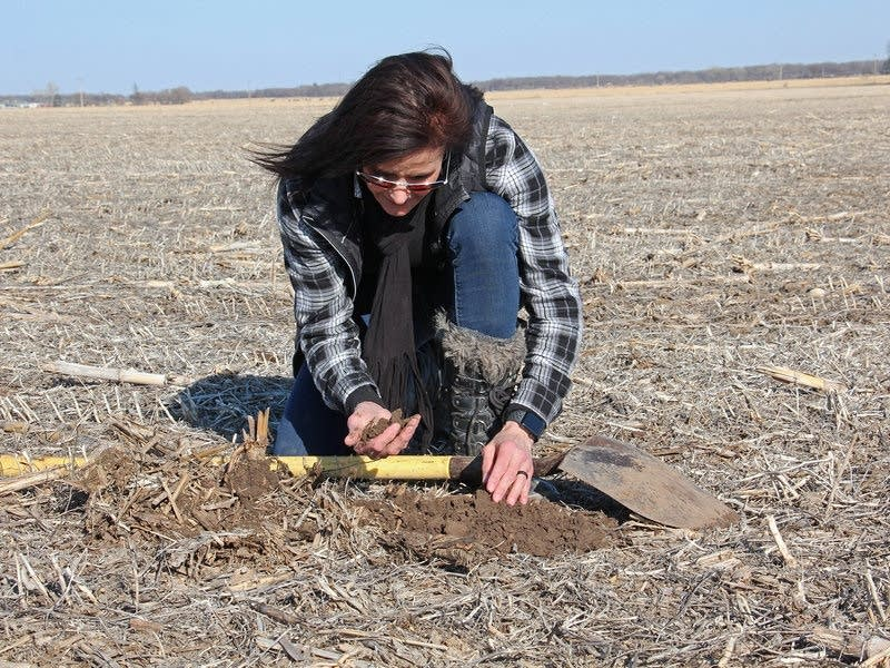 Deb Gangwish inspects soil on her farm near Shelton, Neb.