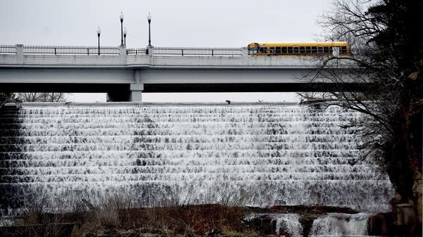 A school bus passes over a bridge near a dam in River Falls, Wis.