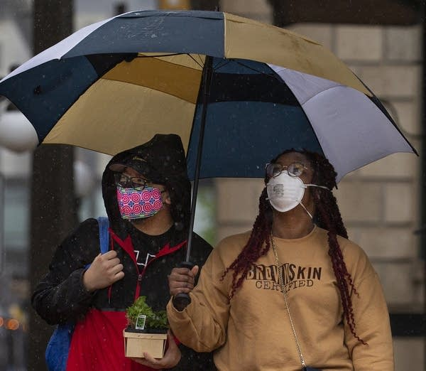 Two people wearing face masks stand under an umbrella