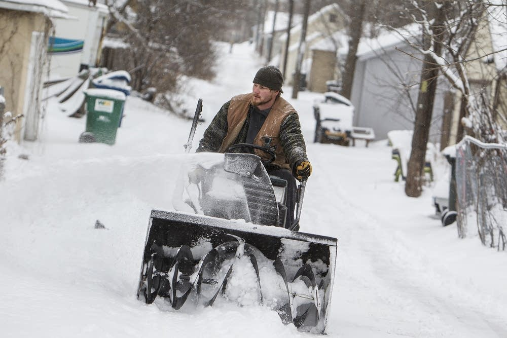 Jason Hintze snowblows the alley for his neighbors