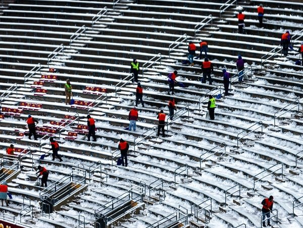 Workers remove snow from the seats at TCF Bank Stadium