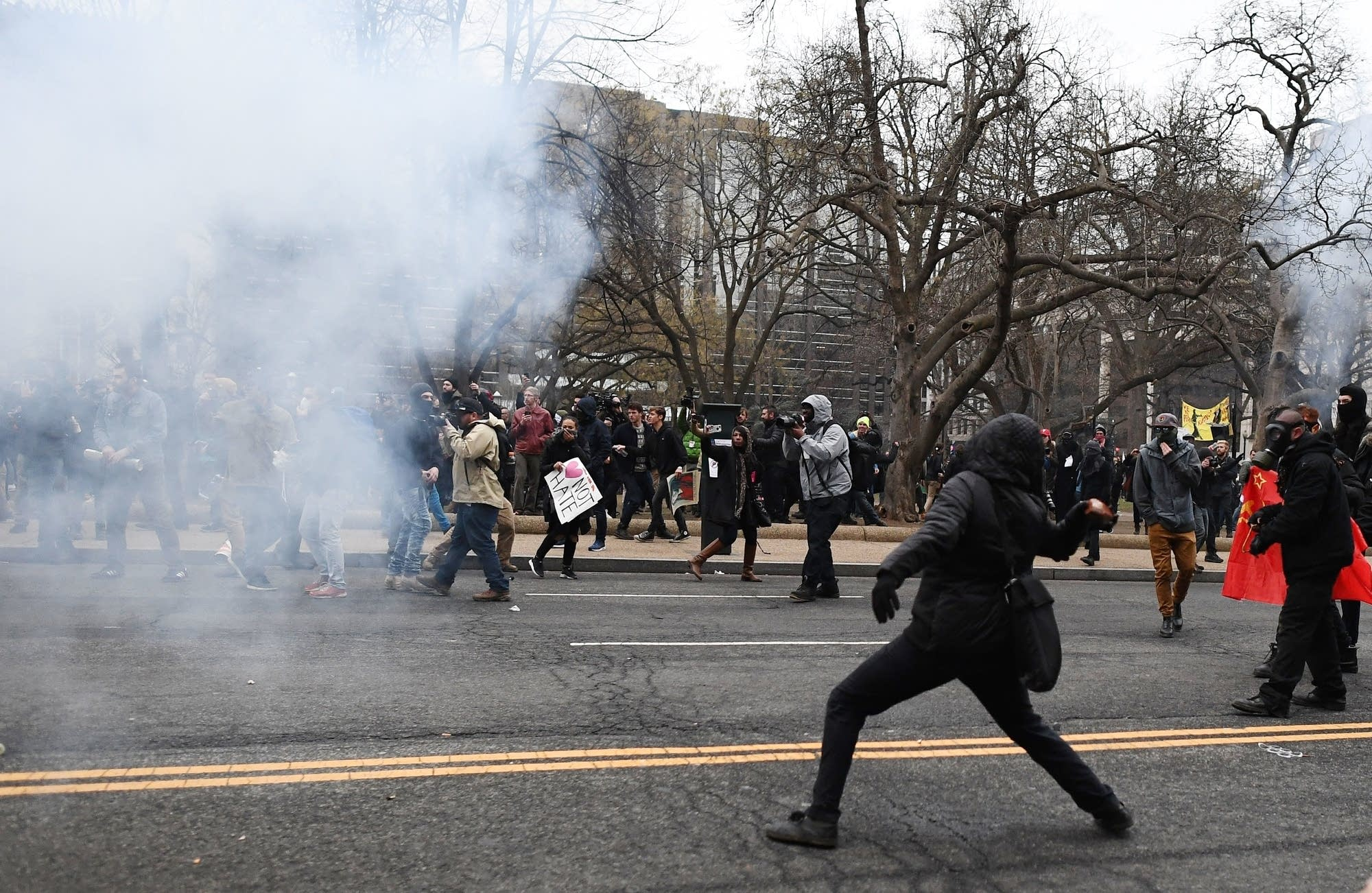 An anti-Trump protester throws a brick at police during clashes.