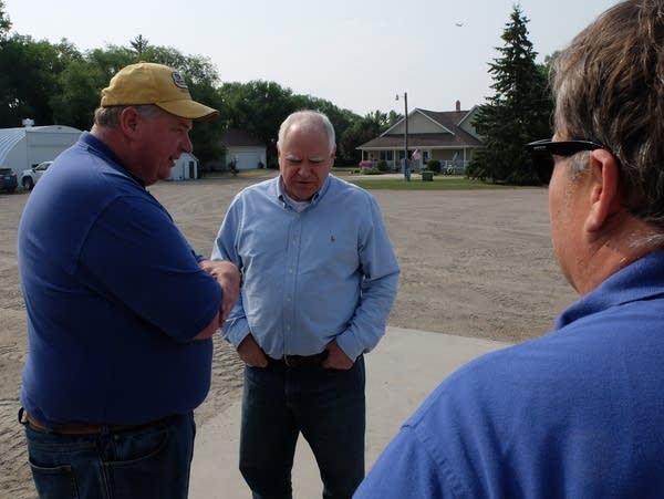 three men talk in a farm yard