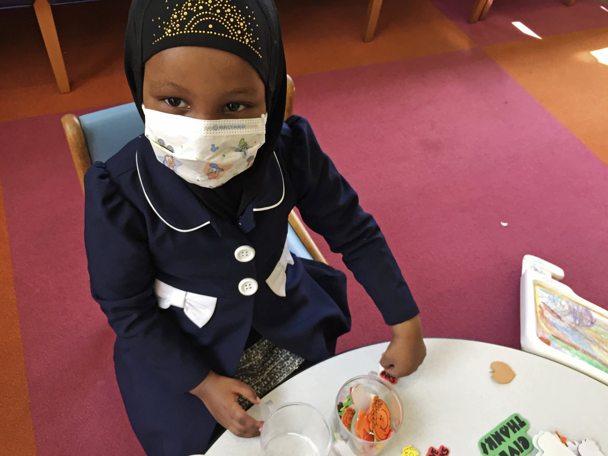 Amira Hassan, of Burnsville, wears a mask to protect her from measles.
